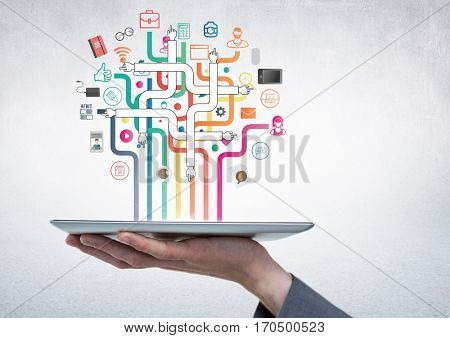 Hand holding a digital tablet against digitally generated application icons on grey white background