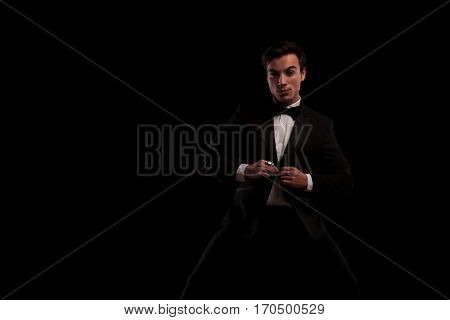 sexy man in tuxedo buttoning his coat and looks at the camera on black backogrund