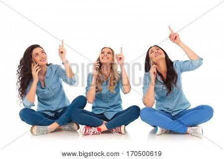 three casual women talking on the phone and pointing fingers up at something on white background
