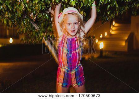 Little girl having fun. Summer night. Happy child. Motion photo. Natural Beauty
