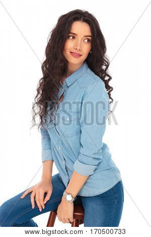 seated casual woman looking over her shoulder to a side on white background