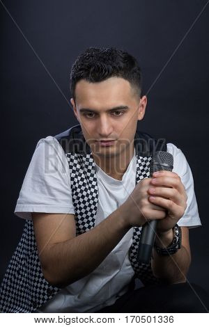 Young Male Black-haired Pop Singer Poses Singing To Microphone