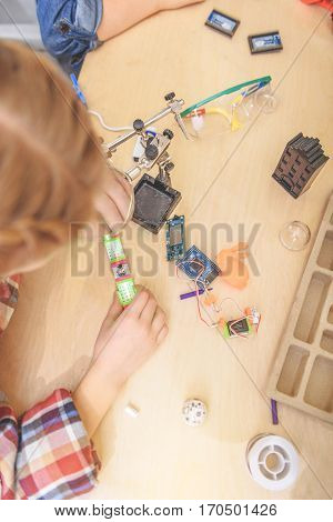 Girl is standing near board. She looking through loupe at little mechanism. Top view
