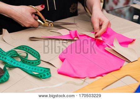 Sewing textile or cloth. Work table of a tailor. Textile tools. Scissors reel of thread measuring tapes and natural fabric. Copy space.