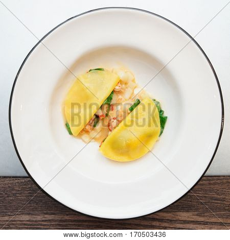 Ravioli-like dish with crayfish, apples and herbs shot from above on restaurant table