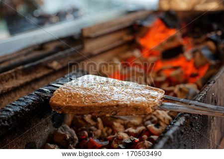 Luleh kebab (minced meat on spits, Middle Eastern staple) being fried on charcoal grill