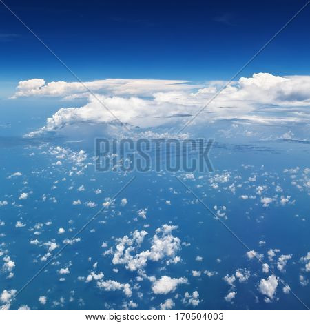 Clear blue sky. Aerial view from passenger cabin through plane window. Aircraft fly in mid air. Flight above ocean and beautiful white cloud. Vacation tour travel background with copy space