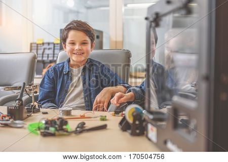 Hilarious little inventor is sitting near wooden desk. He looking at camera