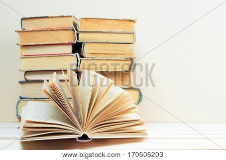 Open book stack of hardback books on wooden table. Back to school. Copy space.