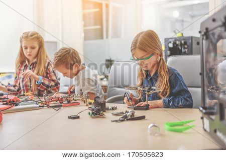 Busy children are sitting near wooden table at workshop. Concentrated girl is using soldering iron