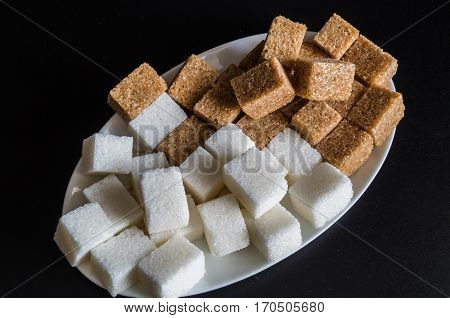 still life with slices of white and brown refined sugar on a white plate on black background