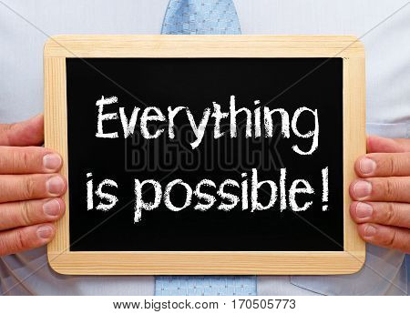 Everything is possible - Businessman holding chalkboard with text