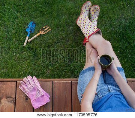 Woman with cup of coffee sitting on a patio wooden deck wearing wellington boots resting after work in the garden