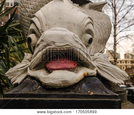 close up view on the characteristic decoration around a street lamp in London large white ornament in the shape of a fish london street lamp