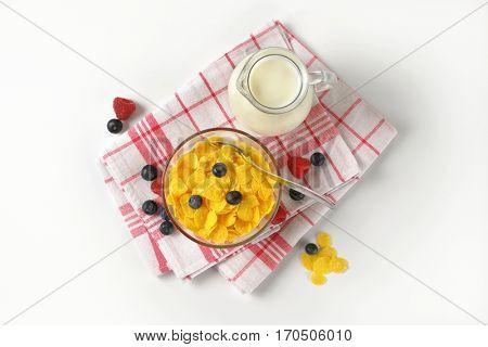 bowl of corn flakes and jug of milk on checkered dishtowel