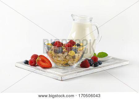 bowl of cereals and berry fruit with jug of milk on wooden cutting board