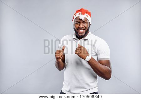 Everything is okay. Joyful young man in red holiday hat is giving thumb up. He is standing and laughing. Isolated and copy space in left side
