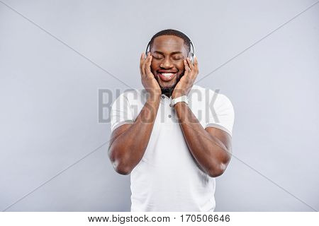 Happy young african man is enjoying music from headphones. His eyes are closed with pleasure. Isolated