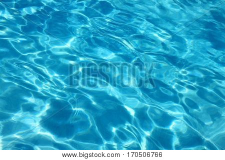 Blue water surface viewed from above in outdoor swimming pool, sun reflection, dimply.