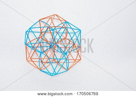 Turquoise and orange handmade three-dimensional model of geometric solid on a white textured background.