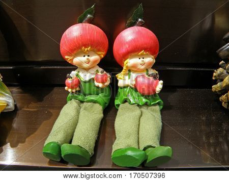 Little Boy and Girl Figurines with Apples in their Hands in Green Outfit and Red Hat sitting Side by Side