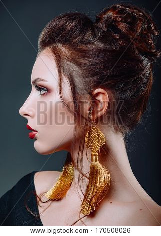 Studio close-up portrait of a beautiful young woman. Profile view