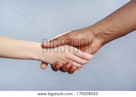 Ethnic friendship. Close up of man and woman shaking hands. They have black and white skin. Isolated on grey background
