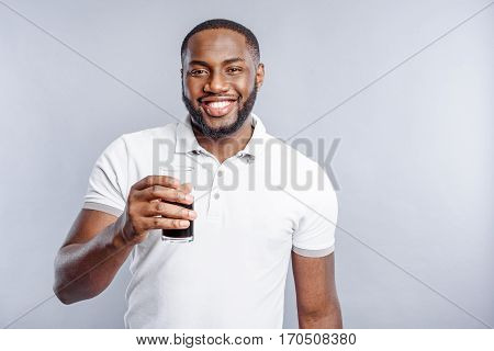 Carefree young african man is standing and holding glass of dark beverage. He is smiling. Isolated on grey background