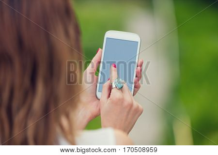 Female using cellphone / texting and surfing the net outdoors.