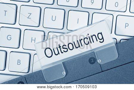 Outsourcing - folder with text on computer keyboard