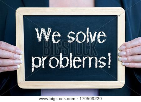 We solve problems - Businesswoman holding chalkboard with text