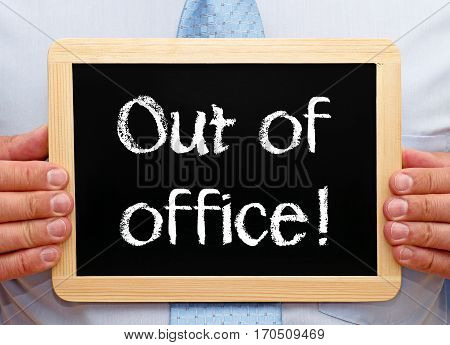Out of office - Businessman holding chalkboard with text