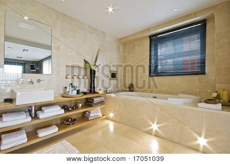 luxury en-suite bathroom with light brown marble and built in plasma tv