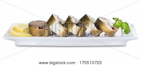 Pieces of mackerel and lemon on a white plate on a white background