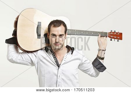 Portrait of young man carrying guitar over his shoulder against gray background