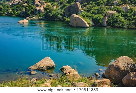 Blue waters of the Tungabhadra River in Hampi, India. River landscape with picturesque rocks on the shore.