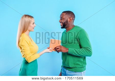 Romantic young african man is giving book to excited caucasian woman. They are looking at each other with love and smiling. Isolated