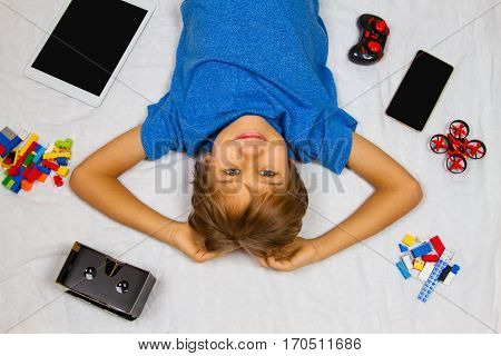 Cute smiling little boy lying in white bed and looking at camera. Mobile phone, tablet computer, drone and VR glasses around him. Top view. Technology, leisure, boys toys concept