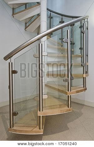 solid newel stairs with wooden steps, and glass and steel rail