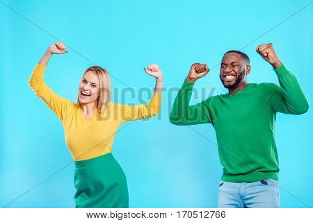 Happy young couple is celebrating their success. They are standing and raising hands in fist. Man and woman are laughing. Isolated