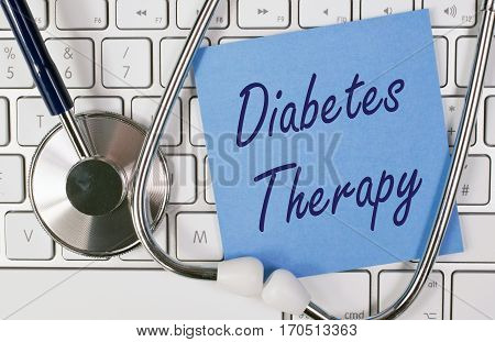 Diabetes Therapy - blue note paper with stethoscope on computer keyboard