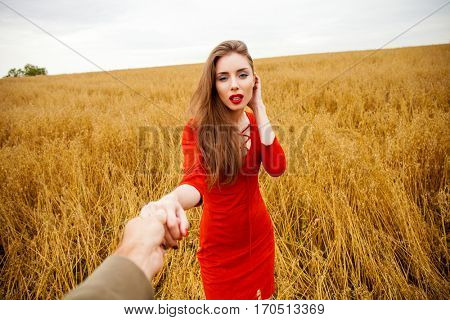 Follow me, Young beautiful brunette woman pulls the arm of her boyfriend in the oats field