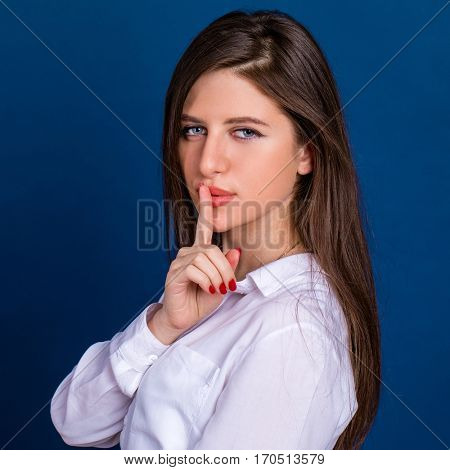 Young beautiful brunette woman has put forefinger to lips as sign of silence, against blue wall