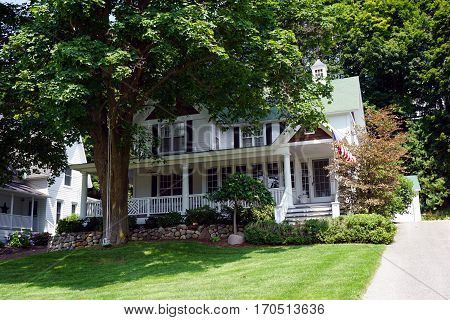 HARBOR SPRINGS, MICHIGAN / UNITED STATES - AUGUST 4, 2016: A large Victorian home with a wraparound porch below the bluff on Fourth Street in Harbor Springs, Michigan.