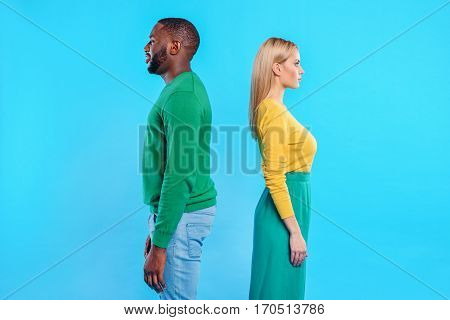 Young woman is took offence at her boyfriend. She is standing back to man and looking forward with sadness. Isolated