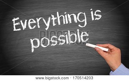 Everything is possible - female hand with chalk writing text
