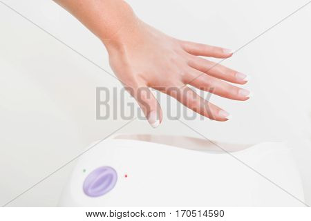 Hand treatment in paraffin bath, white background