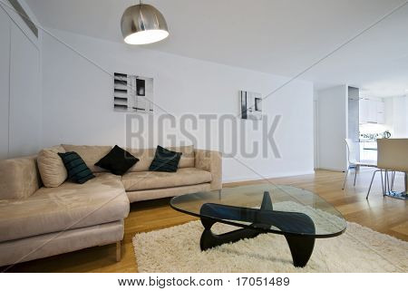 open plan loung with beige sofa, designer coffee table with glass top and dining table