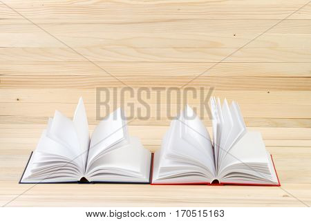 Open hardback books on wooden table. Back to school. Copy space.