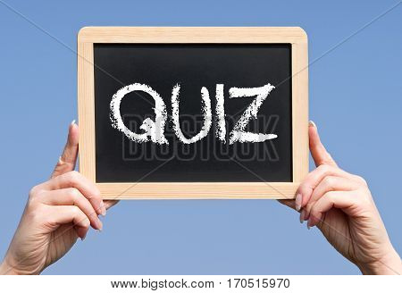 Quiz - female hands holding chalkboard with text